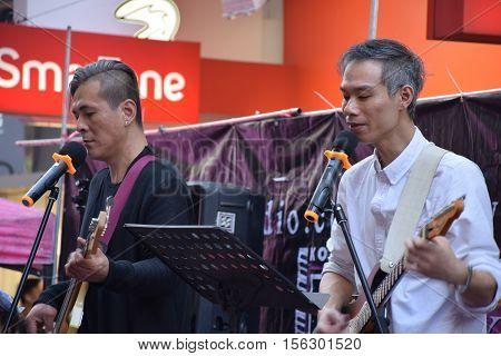 HONG KONG, CHINA - NOVEMBER 13, 2016 - Asian guitarist and bassist playing music and singing