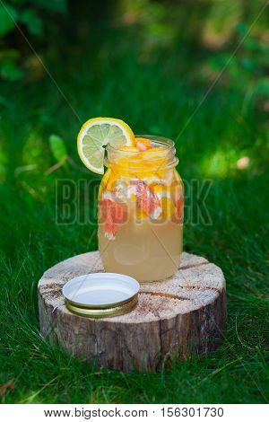 Fresh lemonade from lemon and grapefruit and orange in a jar on a wooden stump. Outdoors