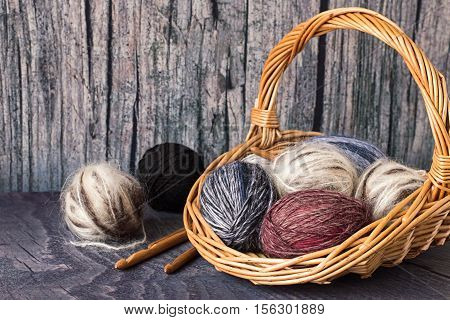 Wicker basket with colored balls of wool yarn and crochet hooks on wooden background.