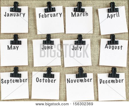 Notice board with twelve clips and note paper showing all months of the year. Blank space for more text