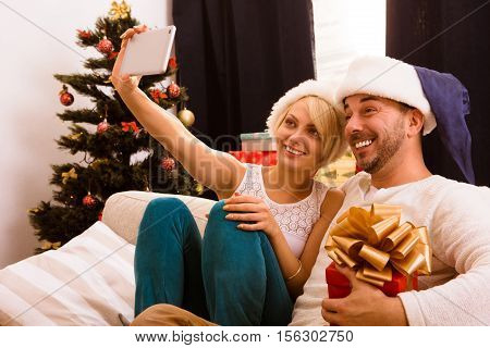 Image of happy Christmas couple making self photos on mobile phone and smiling while staying at home. New Year or Christmas concepts.