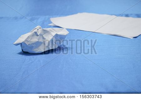 Crumpled paper lump and texture on blue table background in business meeting room with copy space