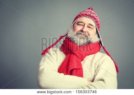 Portrait of Serious Old Man with Beard in Funny Red and White Winter Clothes on Gray Background. Modern Mature Man Concept. Toned Photo with Copy Space.