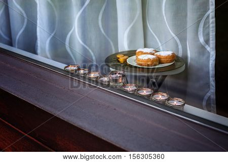 The Symbols of Hanukkah - nine-branched mehorah Hanukiah , sufganiyot and chocolate coins in the window