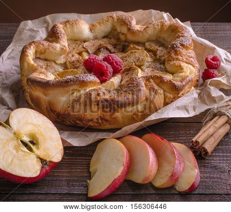 apple pie with cinnamon and raspberry on a wooden table.