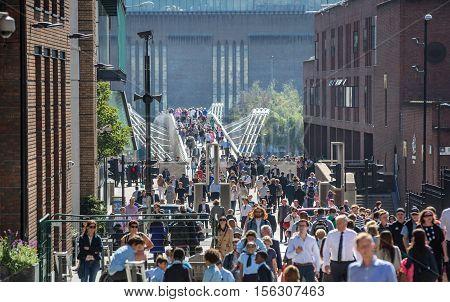 LONDON, UK - SEPTEMBER 10, 2015: Office workers and people walking via Millennium bridge towards st. Paul's cathedral.