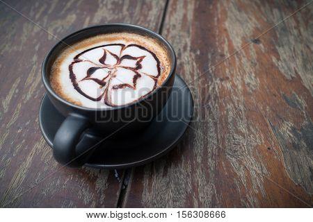 Hot coffee mocha with foam milk art in afternoon break. Coffee mocha on the wood desk.(selective focus vintage effect)