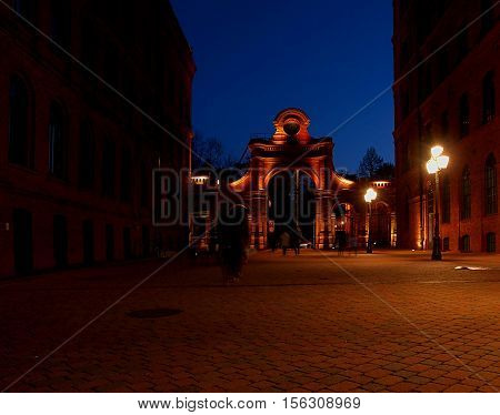 Gate Manufactory. Lodz, Poland November 12, 2016 Illuminated lights, factory gate and walls of the historic factory of Izrael Poznanski, known as Manufaktura shopping center in Lodz.