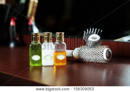 Haircare balms in flask and hairbrush.