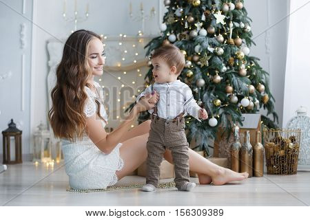 Beautiful brunette woman with long hair,dressed in a short white lace dress,holding New Year's holiday sitting on the floor next to a white elegant Christmas tree with his young son,the boy in pants and a shirt,Christmas portrait of mother and baby