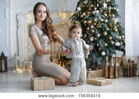Young beautiful woman brunette with long hair, dressed in a short beige dress,standing on his knees,supported his young son,dressed in a beige suit with bow tie next to a festive Christmas tree and gift boxes