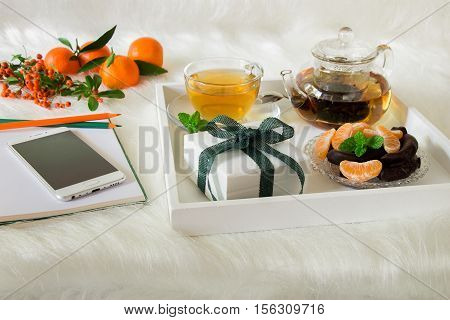 Green mint tea, mandarin slices, chocolate and gift box on tray, near notebook, pens, mobile, mandarins, mountain ash sprig on white artificial fur background. Happy time break and gift.