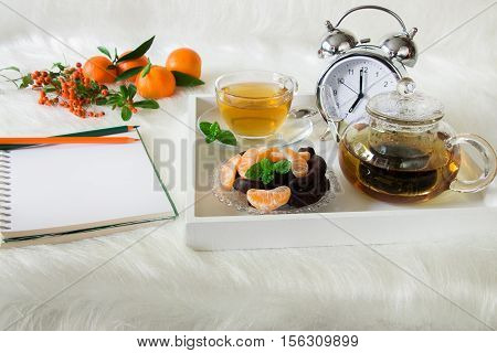 Green mint tea, chocolate, mandarin slices and alarm clock on tray near notebook, pencils, mandarins, mountain ash on white artificial fur background. Morning time breakfast notebook plan preparation.