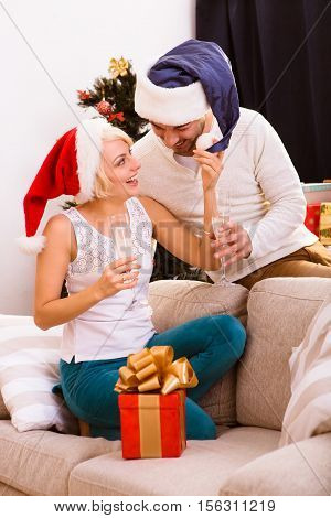 Picture of beautiful happy Christmas couple celebrating New Year at home atmosphere. Cheerful man and woman spending free time all together. New Year or Chrstmas concept.