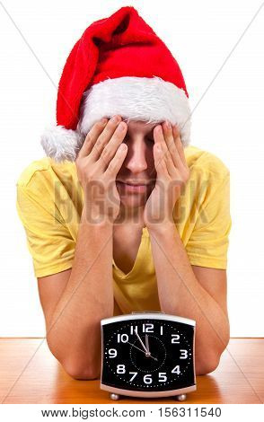 Sad Young Man in Santa's Hat with the Clock at the Table On The White Background