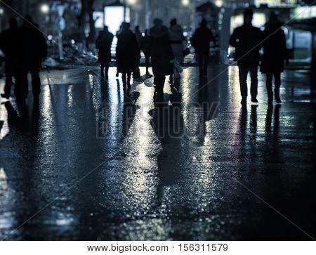 Toned Photo of the Defocused People on the Night Street