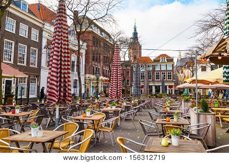 Hague, Netherlands - April 5, 2016: Street view with traditional dutch houses and many restaurant tables in Hague, Holland