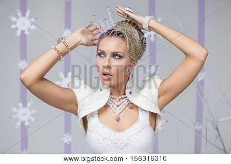 Beautiful young woman with purple makeup,  fancy hairdo and small crystal crown on head. Gorgeous winter bride in felting dress with surprised expression. Copy space.