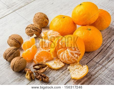 tangerines peeled tangerine tangerine slices and walnuts on a white wooden table