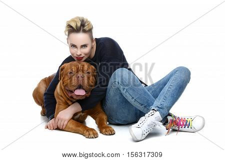 Beautiful young woman in casual clothes hugging big brown dogue de bordeaux dog isolated on white