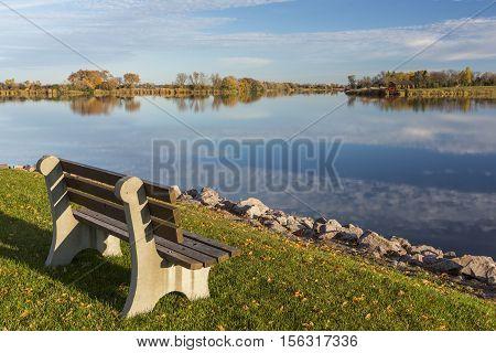 A park bench facing a lake in autumn.