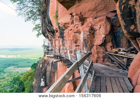 Beautiful Wooden bridge in red cliffside at Wat Phu tok mountain. Bueng Kan Thailand
