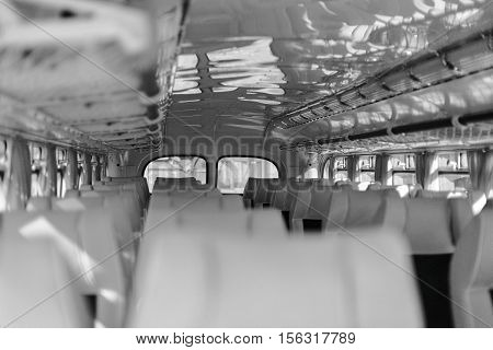 Interior inside of the bus with seats. Black and white.