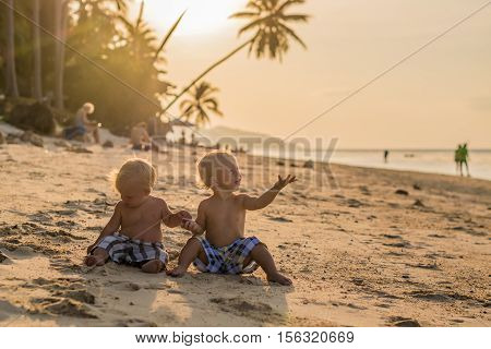 Toddler Boys Sitting On The Beach
