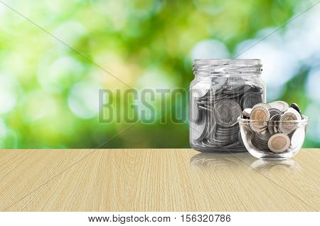 coins in a glass jar on Wood floor savings coins - Investment And Interest Concept saving money concept growing money on piggy bank. isolated on green background