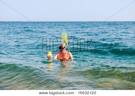 Funny man is snorkeling with fishing net and plastic fish