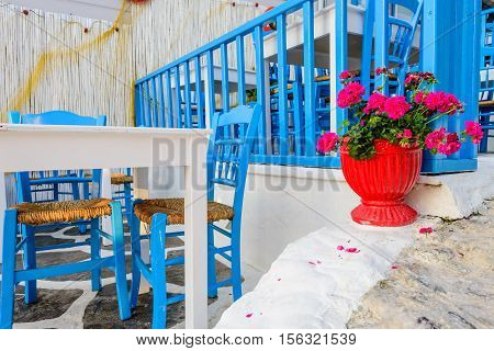 Traditional Greek restaurant on the open air with bright blue chairs and flowers, Kos town, Dodecanese, Greece.