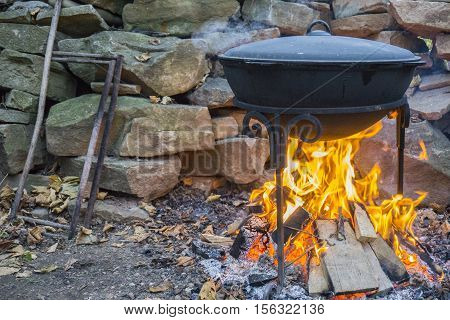 Cooking meat outdoors in cast-iron cauldron. Cooking meat on a fire. Food in a cauldron on a fire. Cooking food in nature on the cauldron.
