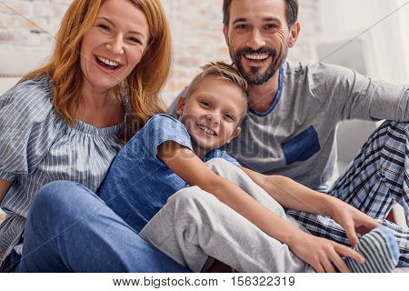 Enjoying time with family. Shot of laughing little boy lying in bed with his parents in morning