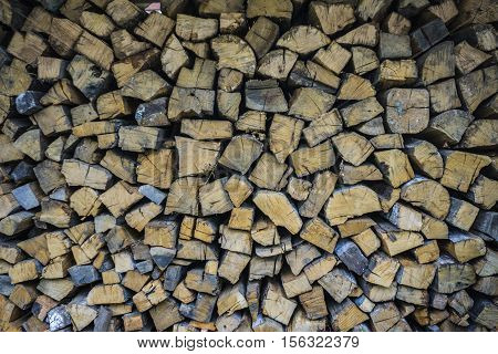 Wall firewood. Background of dry chopped firewood logs in a pile