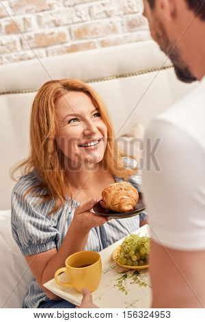 Enjoying day spent with her family. beautiful adult woman holding croissant in her hands and looking at man holding tray