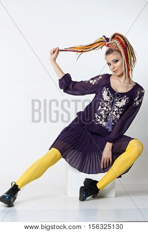 Pretty girl with bright colors dreadlocks. Women in a purple dress with a white ornament and yellow tights sitting on cube. Studio shoot