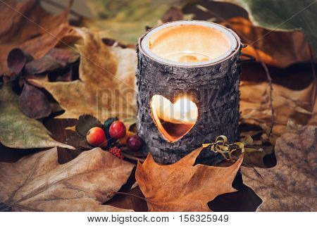 Wood candle holder on fall leaves, still life