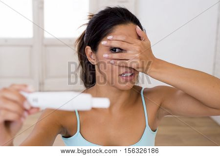 young attractive latin woman holding pregnancy test on bed at home looking at positive result in shock and stress having surprise in girl unwanted maternity concept