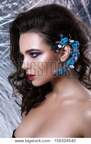 Beauty woman face with beautiful make-up color . Dark hair raised hair jewelry on his neck clean skin beautiful face . Portrait shot in studio on a grey background .