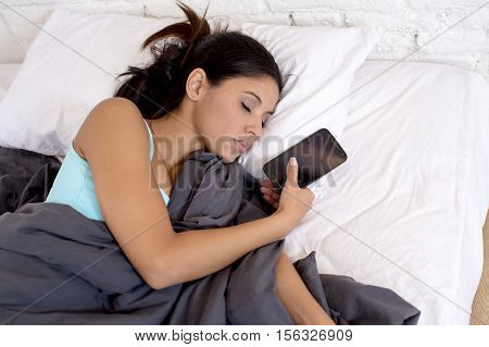 young latin woman sleeping in bed at home together with mobile phone in internet network addiction and technology overuse concept