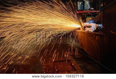 Worker cutting steel with acetylene welding cutting torch and bright sparks in factory