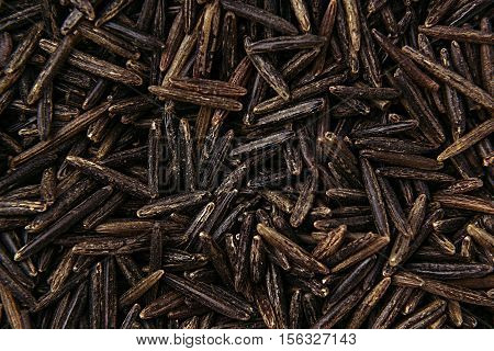 Black rice close-up background. Heap wild brown unpolished rice for vegetarians.
