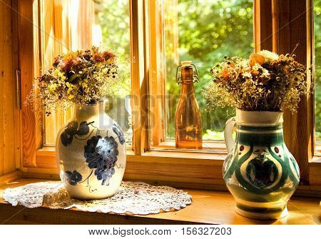 Bouquets of wild flowers in a ceramic jugs on a sill by the window. Light of the setting sun. Rural still life.