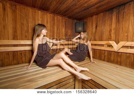 Two beautiful females in sauna.