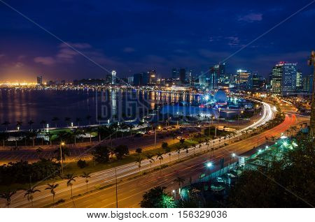 Skyline of Luanda and its seaside during the blue hour. Many lights and high rise buildings.