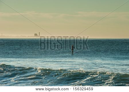 Stand up paddler taking advantage of lull between sets of waves in Ventura.