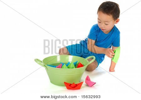 Little Chinese boy with handicap on hand is playing with paper boats isolated over white