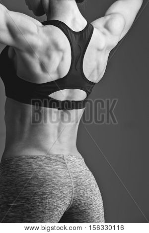 Beautiful fit young woman standing with lifted arms showing back muscles. Studio shot. Fitness. Copy space. Monochrome.