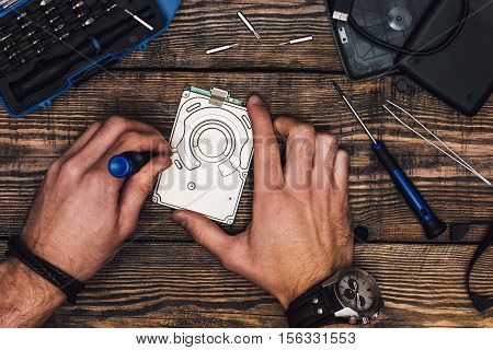 Two Male Hands with Screwdriver Disassemble Hard Drive