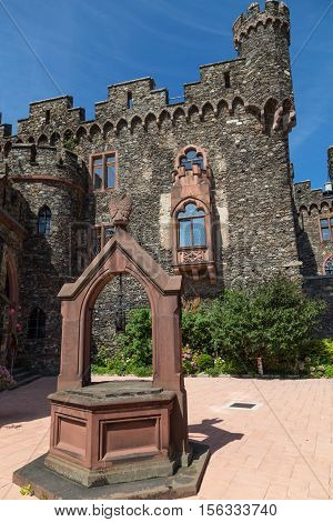 Reichenstein Castle Rhine Valley Germany - UNESCO World Heritage - courtyard with stone well ancient wall with windows and carved turrets against the blue sky